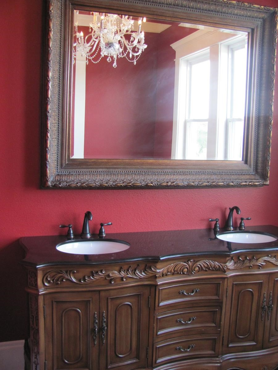 Sinks in Ornate Wooden Cabinets and Large Mirror